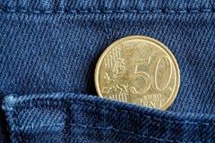Moeda do Euro com uma denominação de 50 euro- centavos no bolso de calças de brim azuis da sarja de Nimes Imagens de Stock Royalty Free