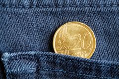 Moeda do Euro com uma denominação de 20 euro- centavos no bolso de calças de brim azuis da sarja de Nimes Fotografia de Stock