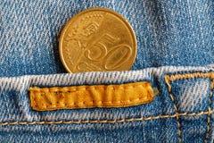 Moeda do Euro com uma denominação de 50 euro- centavos no bolso de calças de brim azuis gastas da sarja de Nimes com listra amare Fotografia de Stock