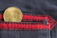 Moeda do Euro com uma denominação de 20 euro- centavos no bolso de calças de brim azuis gastas da sarja de Nimes com listra verme Imagens de Stock