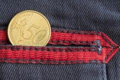 Moeda do Euro com uma denominação de 50 euro- centavos no bolso de calças de brim azuis gastas da sarja de Nimes com listra verme Fotografia de Stock