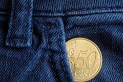 Moeda do Euro com uma denominação de 50 euro- centavos no bolso de calças de brim azuis velhas da sarja de Nimes Foto de Stock Royalty Free