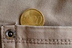 Moeda do Euro com uma denominação de 20 euro- centavos no bolso de calças de brim bege da sarja de Nimes Fotografia de Stock