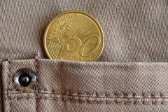 Moeda do Euro com uma denominação de 50 euro- centavos no bolso de calças de brim bege da sarja de Nimes Foto de Stock Royalty Free