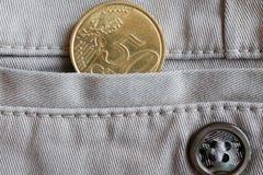 Moeda do Euro com uma denominação de 50 euro- centavos no bolso de calças de brim bege da sarja de Nimes com botão Fotografia de Stock Royalty Free