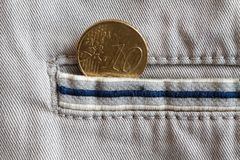Moeda do Euro com uma denominação de 10 euro- centavos no bolso de calças de brim bege da sarja de Nimes com listra azul Fotografia de Stock