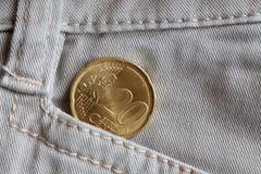Moeda do Euro com uma denominação de 20 euro- centavos no bolso de calças de brim bege velhas da sarja de Nimes Imagens de Stock