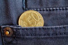 Moeda do Euro com uma denominação de 50 euro- centavos no bolso de calças de brim cinzentas da sarja de Nimes Fotos de Stock Royalty Free