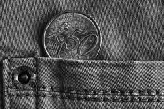 Moeda do Euro com uma denominação de 50 euro- centavos no bolso de calças de brim da sarja de Nimes, tiro monocromático Foto de Stock Royalty Free