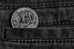 Moeda do Euro com uma denominação de 50 euro- centavos no bolso de calças de brim escuras da sarja de Nimes, tiro monocromático Foto de Stock Royalty Free