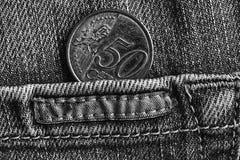 Moeda do Euro com uma denominação de 50 euro- centavos no bolso de calças de brim gastas da sarja de Nimes com listra, tiro monoc Imagem de Stock