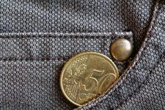 Moeda do Euro com uma denominação de 50 euro- centavos no bolso de calças de brim marrons gastas da sarja de Nimes Imagem de Stock
