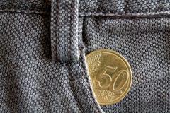 Moeda do Euro com uma denominação de 50 euro- centavos no bolso de calças de brim marrons velhas da sarja de Nimes Imagens de Stock