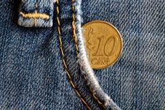 Moeda do Euro com uma denominação de 10 euro- centavos no bolso de calças de brim obsoletas azuis da sarja de Nimes Foto de Stock