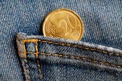 Moeda do Euro com uma denominação de 20 euro- centavos no bolso de calças de brim vestidas azuis da sarja de Nimes Imagem de Stock