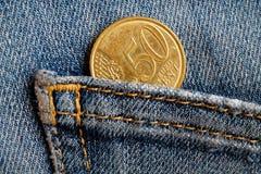 Moeda do Euro com uma denominação de 50 euro- centavos no bolso de calças de brim vestidas azuis da sarja de Nimes Imagens de Stock