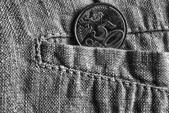 Moeda do Euro com uma denominação de 50 euro- centavos no bolso de calças de linho gastas, tiro monocromático Foto de Stock Royalty Free