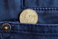 Moeda do Euro com uma denominação de 10 euro- centavos no bolso da obscuridade - calças de brim azuis da sarja de Nimes Fotografia de Stock