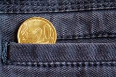 Moeda do Euro com uma denominação de 20 euro- centavos no bolso da obscuridade - calças de brim azuis da sarja de Nimes Imagens de Stock