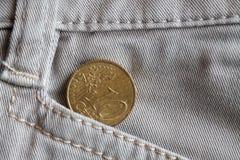 Moeda do Euro com uma denominação de 10 euro- centavos no bolso das calças de brim brancas da sarja de Nimes Fotos de Stock Royalty Free