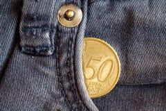 Moeda do Euro com uma denominação de cinqüênta euro- centavos no bolso de calças de brim azuis obsoletas da sarja de Nimes Fotografia de Stock Royalty Free