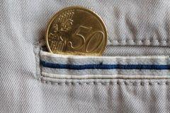 Moeda do Euro com uma denominação de cinqüênta euro- centavos no bolso de calças de brim bege da sarja de Nimes com listra azul Fotografia de Stock Royalty Free