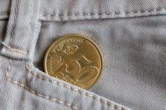 Moeda do Euro com uma denominação de cinqüênta euro- centavos no bolso de calças de brim bege velhas da sarja de Nimes Fotografia de Stock Royalty Free