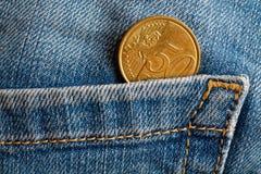 Moeda do Euro com uma denominação de cinqüênta euro- centavos no bolso de calças de brim vestidas azuis velhas da sarja de Nimes Foto de Stock Royalty Free