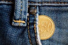 Moeda do Euro com uma denominação de cinqüênta euro- centavos no bolso de calças de brim vestidas velhas da sarja de Nimes Imagens de Stock