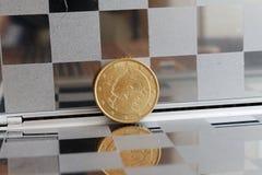 A moeda do Euro com uma denominação de cinqüênta euro- centavos no espelho reflete a carteira, fundo chequered - verso Imagem de Stock