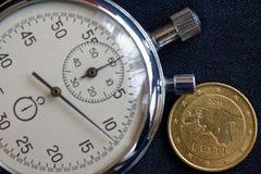 Moeda do Euro com uma denominação de cinqüênta euro- centavos (verso) e de cronômetro em contexto preto gasto da sarja de Nimes - Foto de Stock Royalty Free