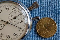 Moeda do Euro com uma denominação de cinqüênta euro- centavos (verso) e de cronômetro no contexto azul da sarja de Nimes - fundo  Fotos de Stock Royalty Free