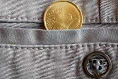 Moeda do Euro com uma denominação de vinte euro- centavos no bolso de calças de brim bege da sarja de Nimes com botão Imagens de Stock