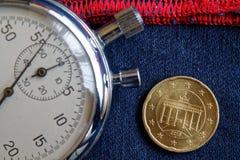 Moeda do Euro com uma denominação de vinte euro- centavos (verso) e de cronômetro em sarja de Nimes azul gasta com contexto verme Foto de Stock