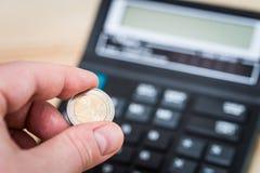 Moeda do euro dois na mão do homem imagem de stock royalty free
