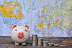Moeda do mealheiro e da pilha no fundo do mapa do mundo Imagens de Stock Royalty Free