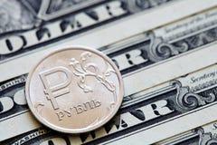 Moeda do rublo de russo em um fundo das notas de dólar Fotografia de Stock Royalty Free