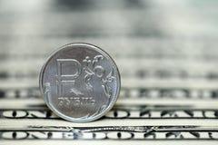 Moeda do rublo de russo em um fundo das notas de dólar Imagem de Stock