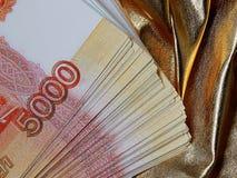 Moeda do russo para 5000 rublos em um fundo do ouro Fotos de Stock Royalty Free