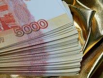 Moeda do russo para 5000 rublos em um fundo do ouro Fotos de Stock