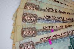 A moeda dos UAE - mil notas do dirham espalharam para fora em um fundo branco Troca de dinheiro fotos de stock royalty free