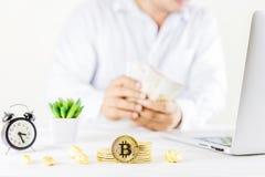 Moeda dourada da moeda de Bitcoin no frasco de vidro na tabela de madeira, homem t foto de stock royalty free