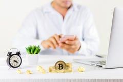 Moeda dourada da moeda de Bitcoin no frasco de vidro na tabela de madeira, homem u imagens de stock