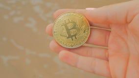 Moeda dourada de BTC como o símbolo do dinheiro virtual eletrônico à disposição vídeos de arquivo