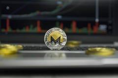 Moeda dourada de Monero com as moedas de ouro que encontram-se ao redor em um teclado preto do gráfico de prata da carta do portá Imagem de Stock Royalty Free