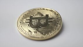 Moeda dourada do bitcoin que gira em um fundo branco filme