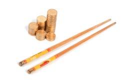 Moeda e chopstick dourados imagem de stock royalty free