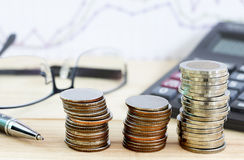 A moeda empilhou o crescimento com vidros e artigos de papelaria na tabela de madeira Foto de Stock