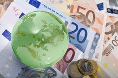 Moeda européia e globo Fotografia de Stock