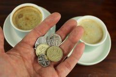Moeda inglesa à disposição com café dois no fundo Foto de Stock Royalty Free